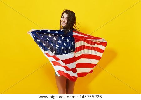 Beautiful patriotic young woman with the American flag held in her outstretched hands over bright yellow background. 4th july Independence Day concept