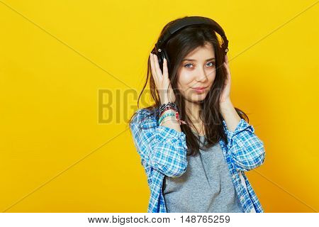 Pretty young woman listens and enjoys the music in headphones against the colorful yellow wall with copyspace