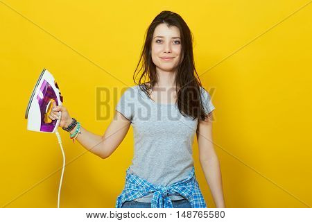 Young woman with iron in her hand over yellow background. Young and beautiful housewife
