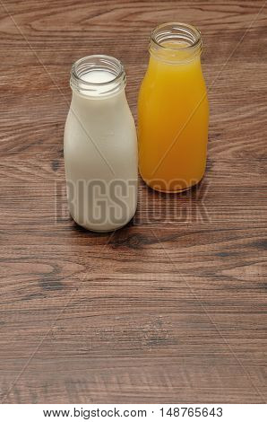 Milk and orange juice in bottles isolated against a wooden background