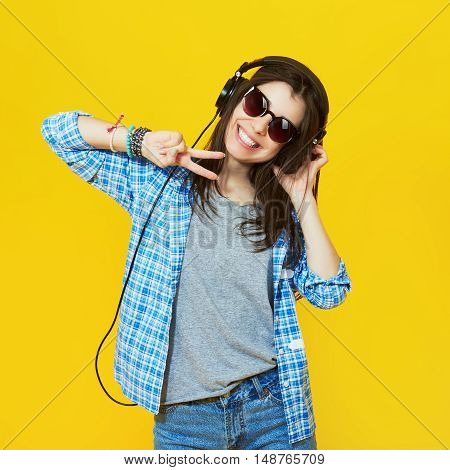 Fashion pretty cool girl wearing a sunglasses and headphones having fun over yellow background