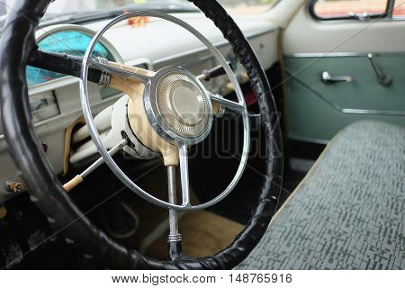The wheel and part of the interior of an old passenger car of the mid-twentieth century