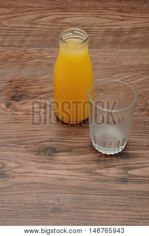 Orange juice in a bottle with an empty glass isolated against a wooden background