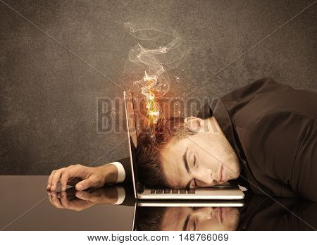 A frustrated businessman resting his head on a keyboard and shouting with his hair on smoke, catching fire