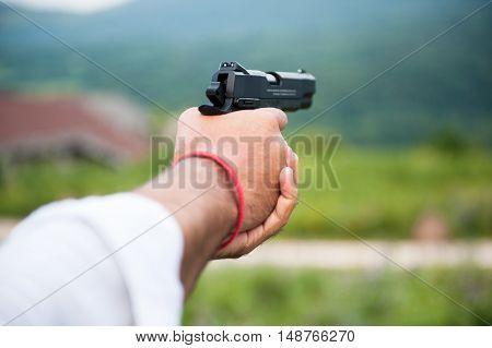 hands of adult man aiming black gun