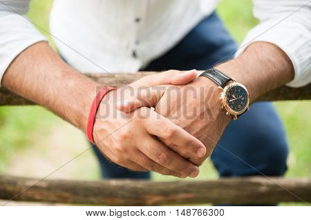 hands adult male wearing watch and bracelet leaning on wooden fence