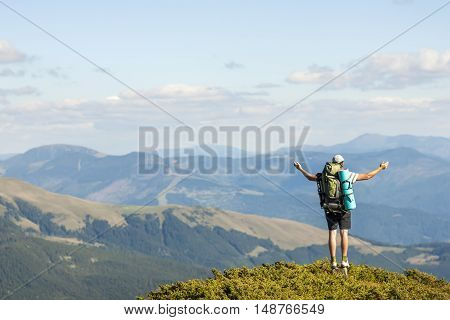 Hiker standing on top of mountain. Unity with nature concept.