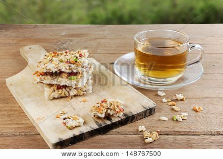 Crispy grains granola bar or rice biscuits with a glass cup of hot tea on wood table.