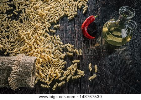 Fusilli pasta scattered from sack, chili and oil on the dark wooden table