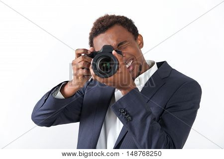 Close up of African American man holding a photo camera and looking at the viewer. Concept of freelance work.