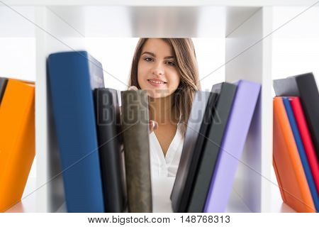Smiling young lady taking a book from shelf. Concept of knowledge and research importance in science and business