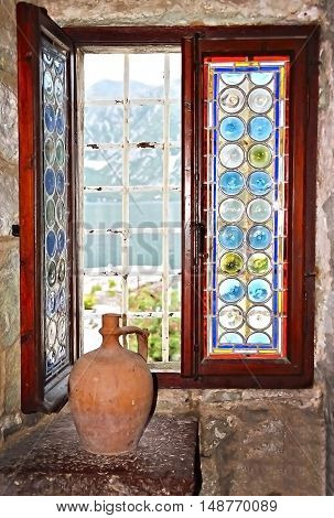 Stained glass window and old pitcher on the Island of Virgin of the Rocks in the Bay of Kotor in Montenegro