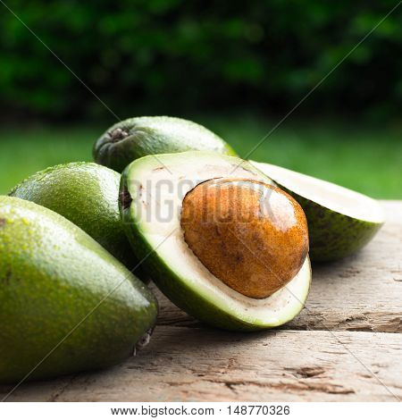 fresh avocado and slices avocado on old wooden background Selected focus