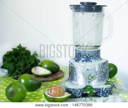 Broken avocado and banana smoothie and smoothie maker with greens