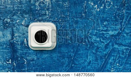 Background. Call button on the blue wall.