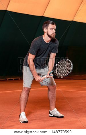 Man playing tennis and waiting for the service