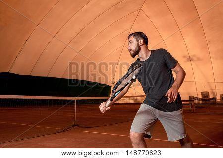 Young man tennis player on court. beats kick