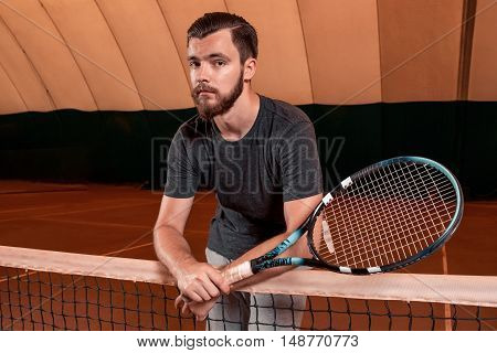 Successful sportsman with racket at the tennis court. Healthy lifestyle