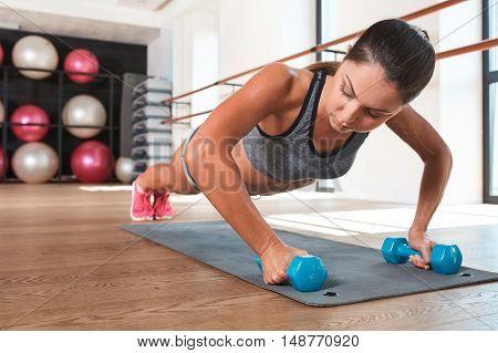 Gorgeous suntanned brunette doing exercises a the gym. girl doing some push ups on a dumbbell