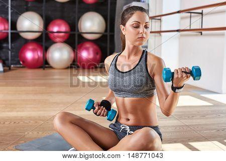 Gorgeous suntanned brunette doing exercises a the gym. girl doing lifting dumbbells