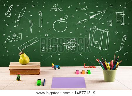 Wooden school desk with stuff and blackboard full of drawings concept