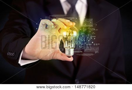 A serious business person has a complex solution concept illustrated by glowing glass light bulb in his hand with graph charts, numbers, lines, calculations.