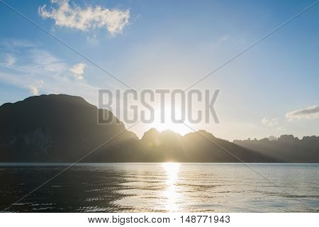 Sun rise behind mountain at Khao Sok National Park Surat Thani Thailand. - with len flare