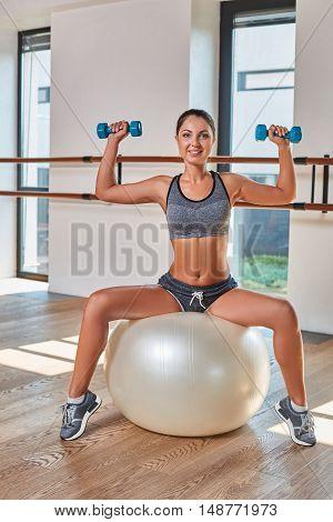 Gorgeous suntanned brunette doing exercises a the gym. girl doing lifting dumbbells on fitball