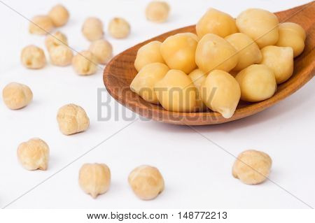 freshly cooked chickpeas over spoon on white background.