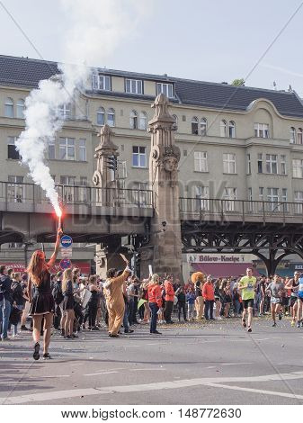 BERLIN GERMANY - SEPTEMBER 25 2016: Spectators With A Torch And Runners At Berlin Marathon 2016