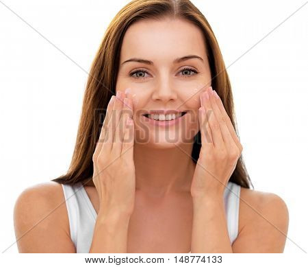 Beautiful young woman applying cream onto face, on white background