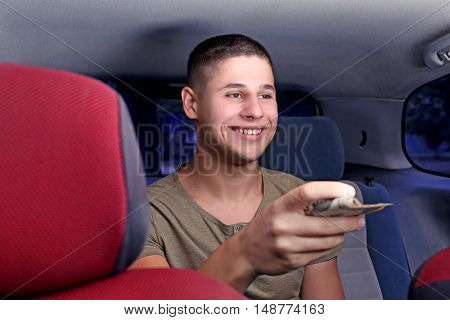 Handsome man paying for taxi