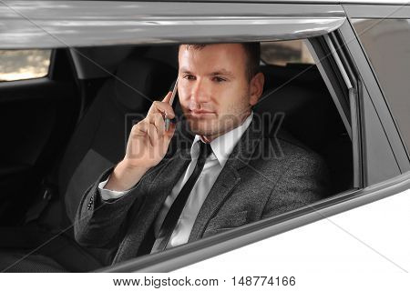 Businessman speaking by cellphone in  a car