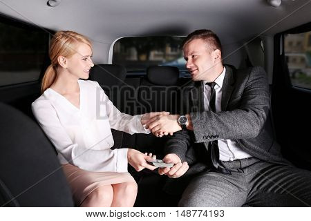 Business deal. Business people handshaking in car