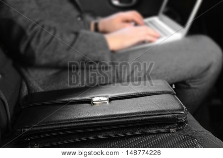 Black leather briefcase and businessman with laptop in car