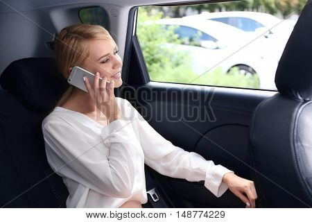 Businesswoman speaking by cellphone in  a car