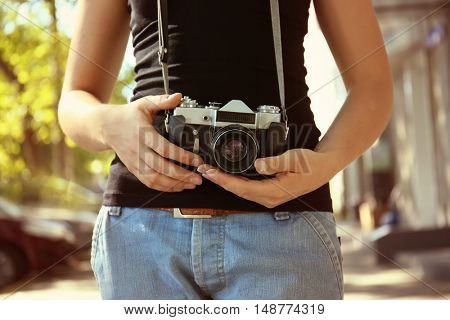 Woman with vintage camera, outdoors