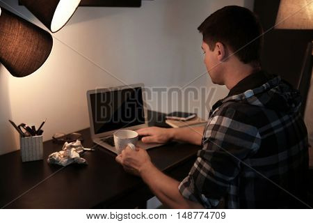 Tired young man working on laptop late in evening with cup of coffee