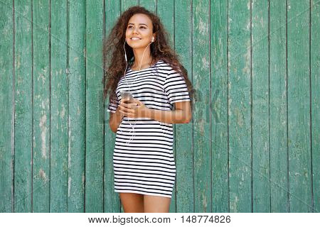 African American girl listening music on wooden background