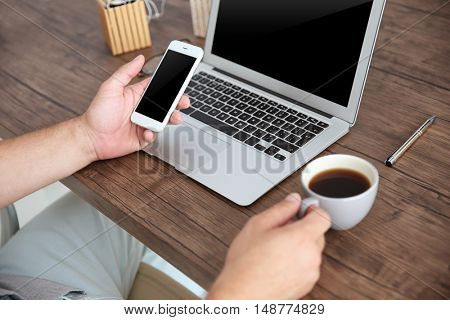 Close up of male hands with mobile phone and cup of coffee