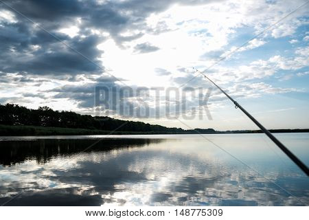 Fisherman sport hobby fishing rod or spinning reel on the river. Fishing on sunrise. beautiful sunrise on the river is reflected in water.