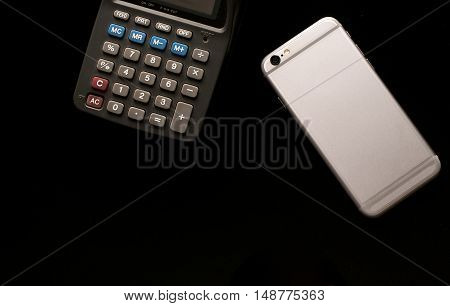 Smartphone and calculator use in business office black background