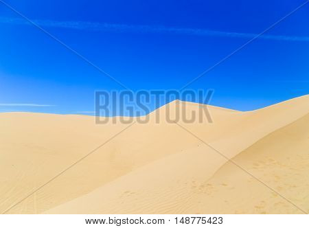 Footprints in the sand of the Algodones Dunes near Winterhaven in California USA with blue sky.