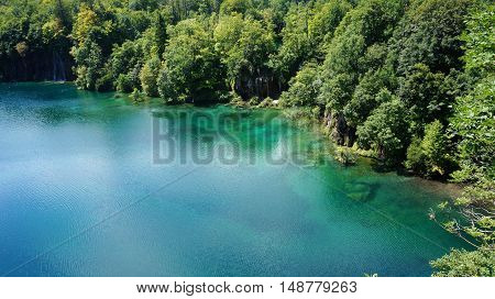 Plitvice Lakes National Park in Croatia. Deep forest lake with crystal clear water in the sunshine