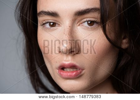 skincare and beauty concept, portrait of a calm, pretty freckled girl looking into camera