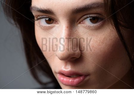 skincare and beauty concept, close up of a peaceful young freckled girl looking into camera