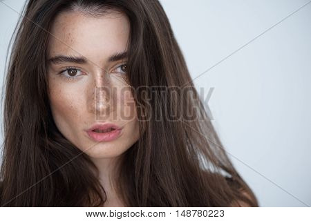 beauty and skin care concept, close up of a calm young brunette looking into camera