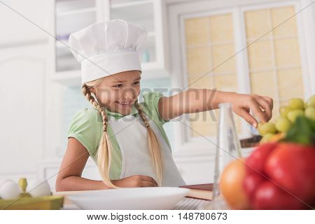 Cute girl wants to eat grape in kitchen. She is taking fruit with desire and smiling. Child is standing near table in chef clothing