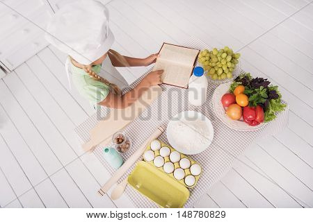 Top view of little girl reading recipe in kitchen. She is standing near table with fresh food