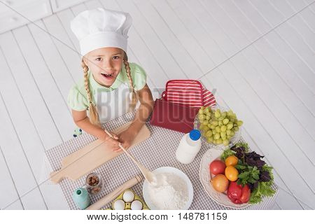 Happy girl is cooking pastry in kitchen. She is having fun with flour and smiling. Child is looking at camera and laughing